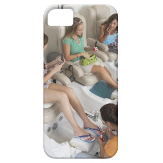 Three young women receiving pedicure in beauty iPhone 5 cover