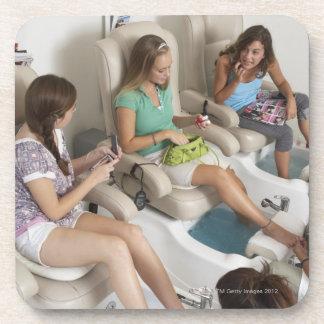 Three young women receiving pedicure in beauty coaster