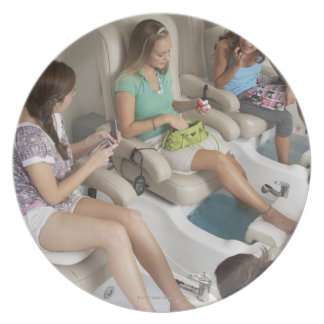 Three young women receiving pedicure in beauty melamine plate