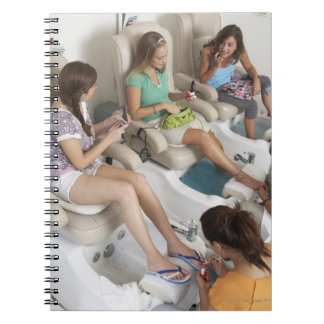 Three young women receiving pedicure in beauty spiral notebook