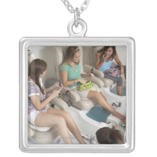 Three young women receiving pedicure in beauty square pendant necklace