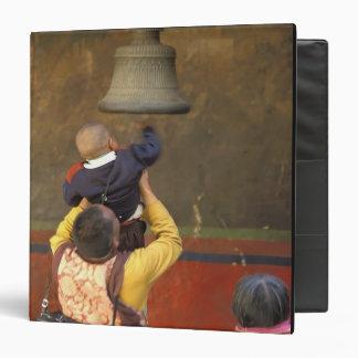 Tibetan Buddhist monk lifting a boy to ring a Binder