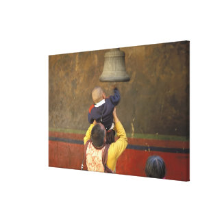 Tibetan Buddhist monk lifting a boy to ring a Canvas Print