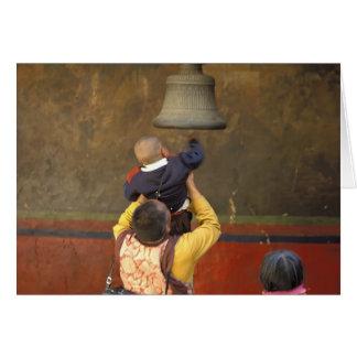 Tibetan Buddhist monk lifting a boy to ring a Card