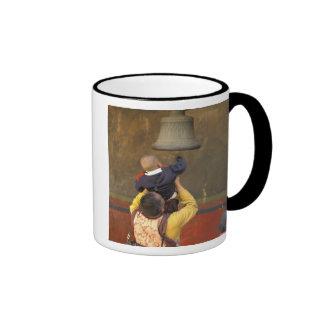 Tibetan Buddhist monk lifting a boy to ring a Ringer Mug