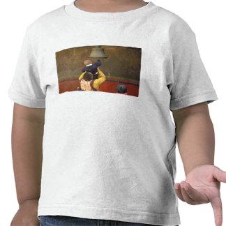 Tibetan Buddhist monk lifting a boy to ring a Tee Shirt