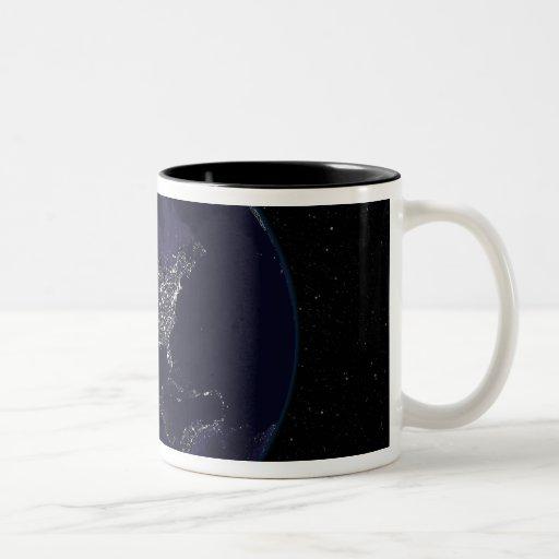 Tierra llena en la noche que muestra las luces 4 tazas de café