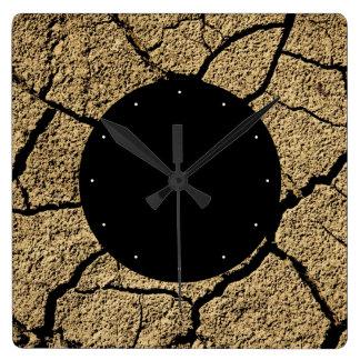 Tierra seca con tierra agrietada en sequía reloj