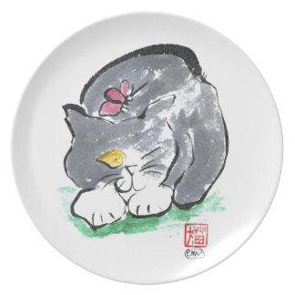 Tierras de la mariposa en el gato gris del plato para fiesta