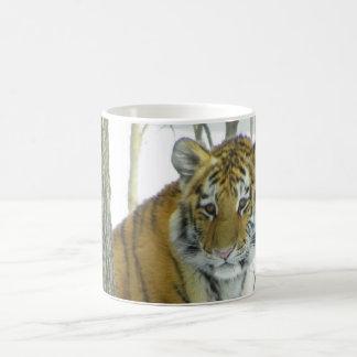 Tiger Cub In Snow Peeking Around Tree Coffee Mug