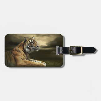 Tiger looking and sitting under dramatic sky bag tag