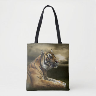 Tiger looking and sitting under dramatic sky tote bag