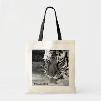 Tigre de consumición en el agujero de riego blanco bolsas