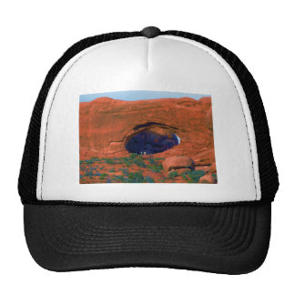 Tiny tourists stand in an arch trucker hat