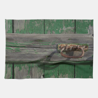 Tirador de puerta oxidado en puerta verde toallas de cocina