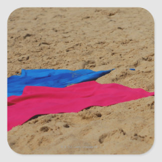 Toallas coloreadas en la playa arenosa pegatina cuadrada
