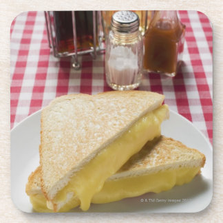 Toasted cheese sandwiches on plate, vinegar, beverage coaster