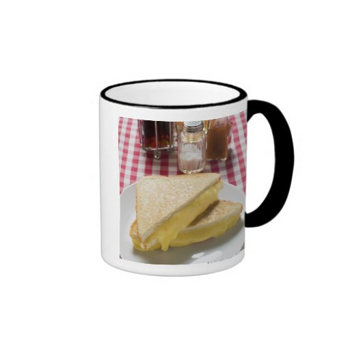 Toasted cheese sandwiches on plate, vinegar, mug