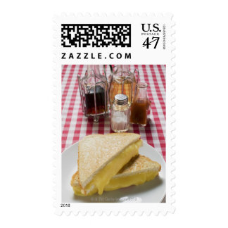 Toasted cheese sandwiches on plate, vinegar, postage