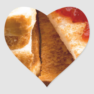 Toasted slices of bread with strawberry jam heart sticker