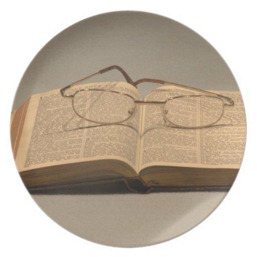 Todavía vida con la biblia y los vidrios de lectur platos