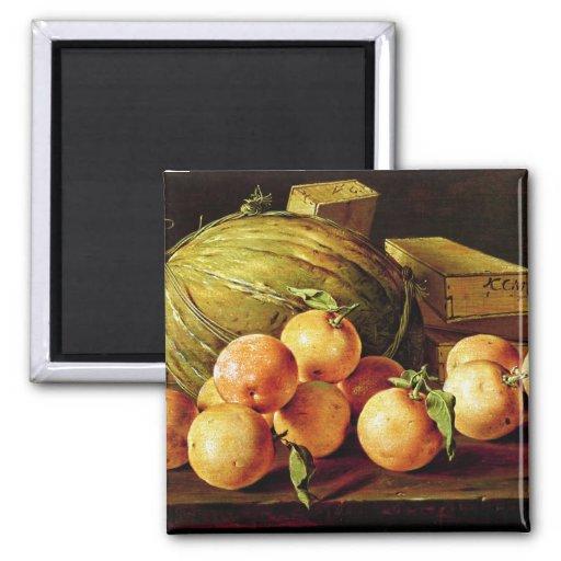 Todavía vida de naranjas, de melones y de cajas imán para frigorífico