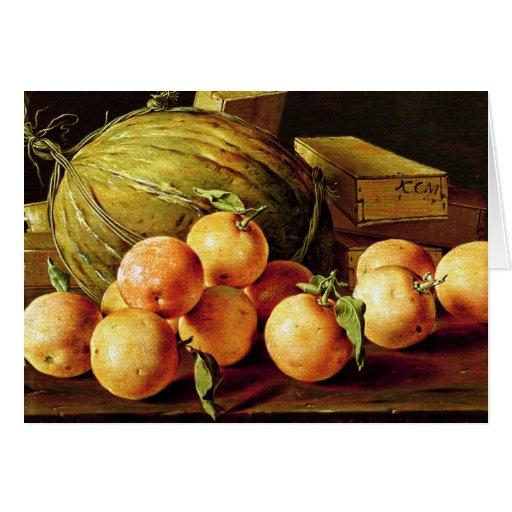 Todavía vida de naranjas, de melones y de cajas felicitación
