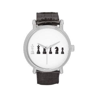 Todos los pedazos de un ajedrez blancos negros relojes