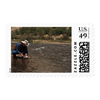Toma panorámica del hombre para el oro en el río timbre postal