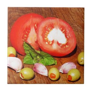 tomate con las aceitunas y el ajo rellenos azulejo cuadrado pequeño