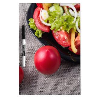 Tomates frescos y ensalada de la opinión superior pizarras