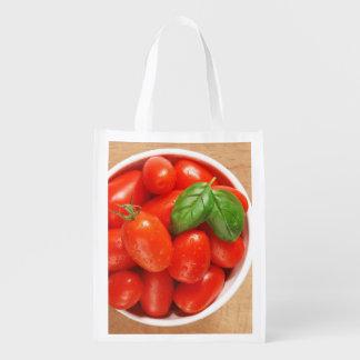 Tomates maduros rojos con albahaca bolsa de la compra