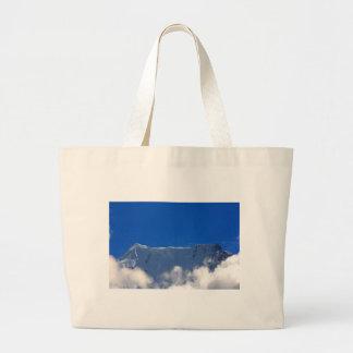 Top de la montaña sobre las nubes bolsas