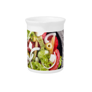 Top view of a small bowl of vegetables salad beverage pitcher
