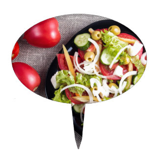 Top view of a small plate of raw salad cake topper