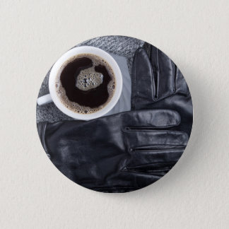 Top view of a white cup of coffee and black gloves button