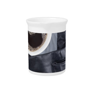Top view of a white cup of coffee and black gloves drink pitcher