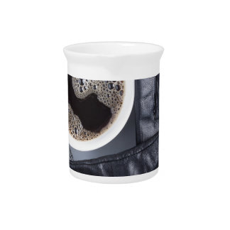 Top view of a white cup of coffee and gray woolen beverage pitcher