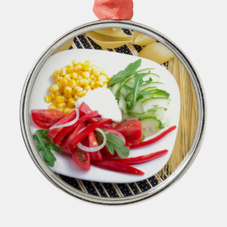 Top view of a white plate with salad metal ornament