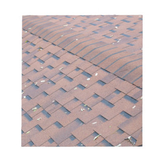 Top view of brown roof shingles with a few autumn notepad