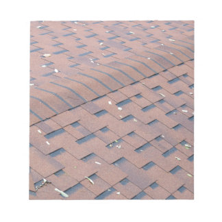 Top view of brown roof shingles with a few fallen notepad