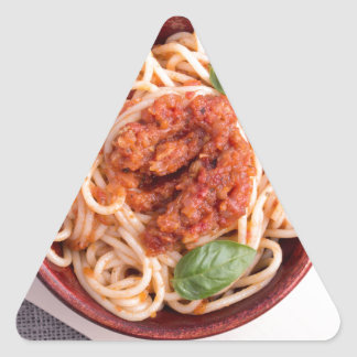 Top view of cooked spaghetti with tomato relish triangle sticker