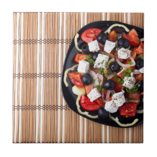 Top view of fresh vegetarian salad on a black ceramic tile