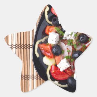 Top view of fresh vegetarian salad on a black star sticker