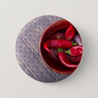 Top view of hot red chili peppers in a brown wood button
