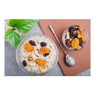Top view of oatmeal porridge with raisins, cashews poster