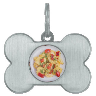 Top view of the pieces of potato stew with vegetab pet ID tag