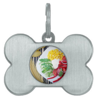 Top view of the vegetarian dish of raw vegetables pet ID tag