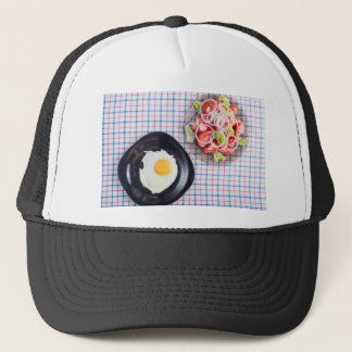 Top view on a black plate with a fried egg trucker hat
