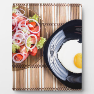 Top view on a fried egg and a salad of tomato plaque